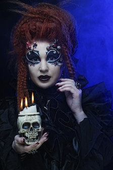 Gothic vampire woman with skull, close up