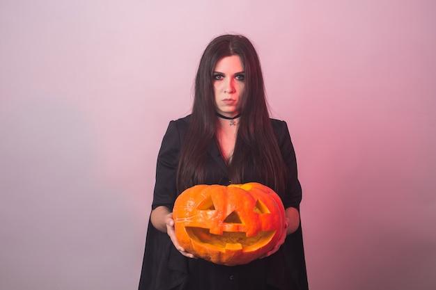 새겨진 된 호박 마녀 할로윈 의상에서 고딕 젊은 여자.