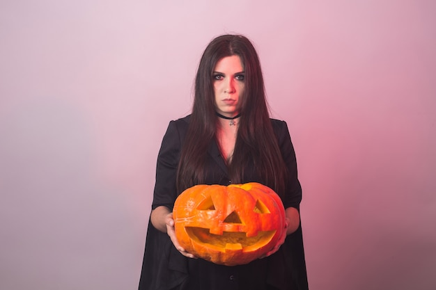 Gothic young woman in witch halloween costume with a carved pumpkin.