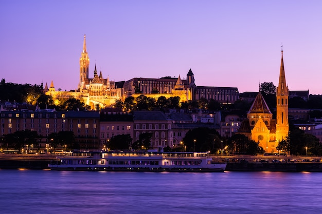 The gothical matthias church, in the buda district near the fisherman's bastion at sunset with sightseeing ship