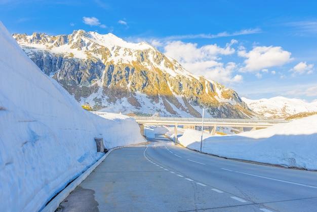 스위스의 햇빛 아래 눈으로 덮인 산으로 둘러싸인 고 타드 패스