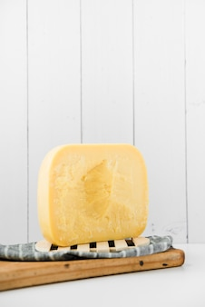 Gouda cheese on wooden chopping board against white wall