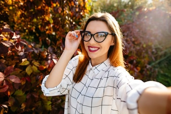 Gougeus model takes selfie while holding her glasses with one hand in autumn garden.