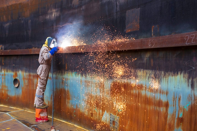 Строжка сварка искровым огнем промышленный сварщик носить защитную маску защитную маску ремонт конструкции резервуар масляный шов для новой детали в ограниченном пространстве