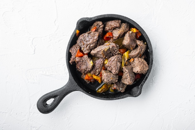 Гуляш, тушеная говядина, на чугунной сковороде, на белой каменной поверхности
