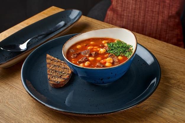 Гуляш, говядина, помидоры, суп из копченой паприки на столе в ресторане