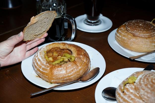 Гуляш подается в миске для хлеба на белой тарелке. ресторан в чехии. чешская кухня. рука поднимает крышку хлеба