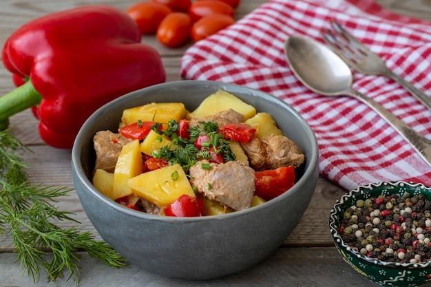 Гуляш с картофелем, мясным перцем и специями на деревянном столе