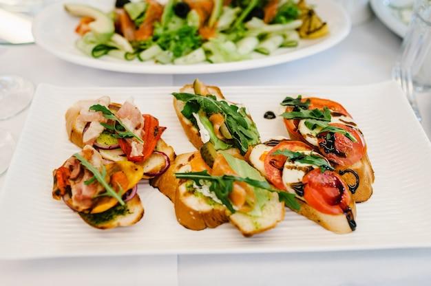Изысканные закуски, фото бутерброда на тарелке, кростини с разными начинками. вкусные. передний план. ассорти итальянских закусок брускетта. разнообразие мини-бутербродов.