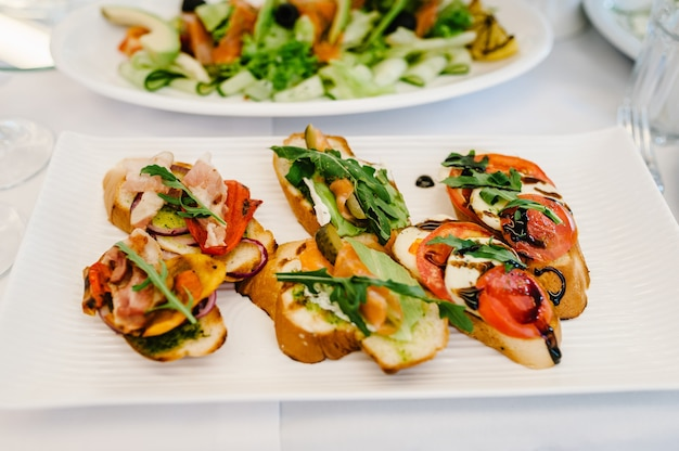 Gourmet appetizers, photo of sandwich on plate, crostini with different toppings. delicious. front view. assorted italian appetizer bruschetta. variety of mini sandwiches.