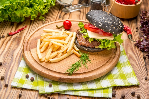 Gourmet black burger with spicy sauce on wooden table