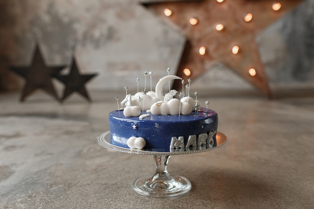 Gourmet blue birthday cake with white decor and candle number one on glass stand in loft