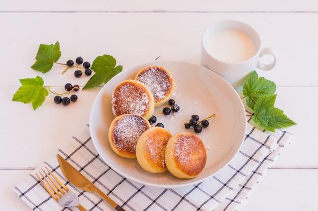 Изысканный завтрак - творожные оладьи, сырники, творожные оладьи с черной смородиной и сахарной пудрой в белой тарелке. выборочный фокус.
