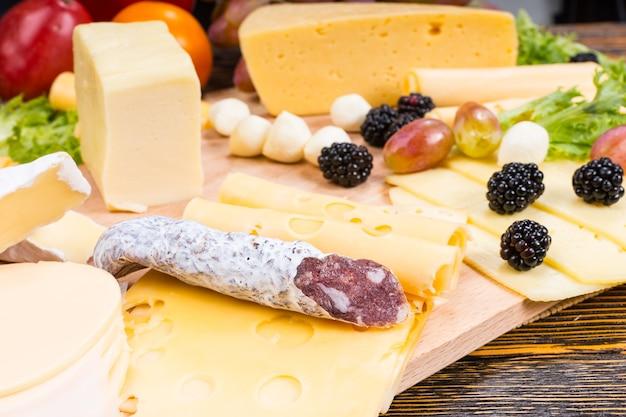 さまざまなチーズ、硬化肉ソーセージ、新鮮なフルーツを木目調の素朴な木製テーブルで提供するグルメチーズボード