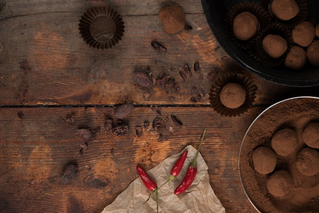 Gourmet cocolate and chilil truffles on a wooden background.