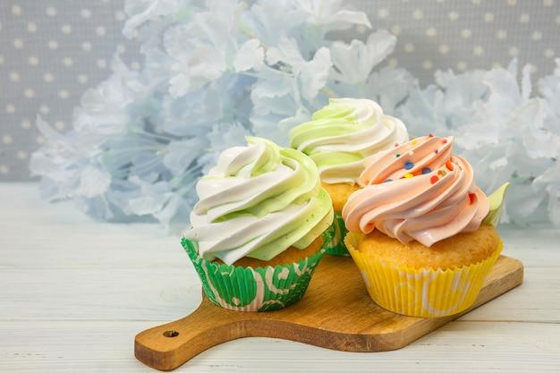 크림색과 색의 뿌리를 곁들인 미식가 컵 케이크