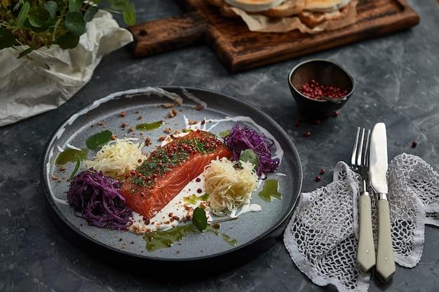 Блюдо для гурманов. копченый лосось с овощами. блюдо из лосося для ресторана