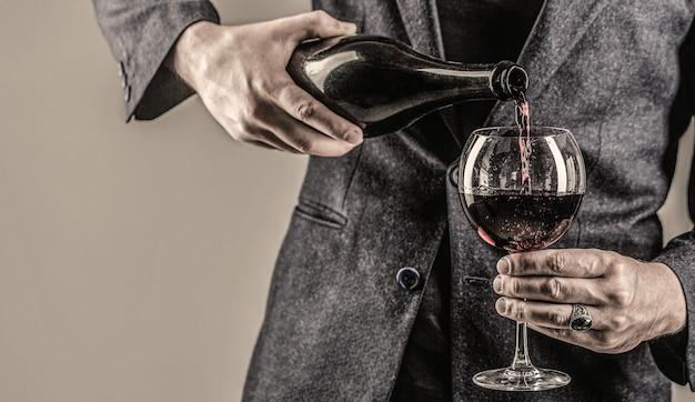 Бутылка напитка для гурманов, бокал для красного вина, сомелье, дегустация. официант наливает вино