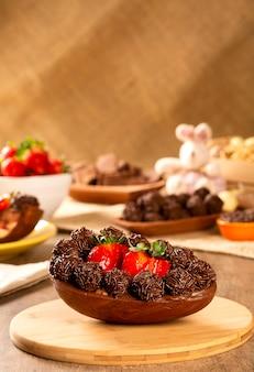 초콜릿과 딸기로 채워진 미식가 부활절 달걀. 푸딩 크림, 부활절 디저트와 함께 부활절 달걀. 부활절 개념.