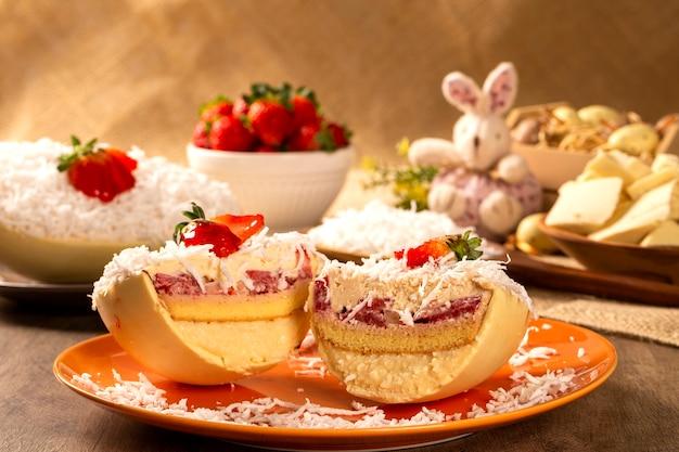 코코넛 크림, 딸기 및 초콜릿으로 채워진 미식가 부활절 달걀. 푸딩 크림, 부활절 디저트와 함께 부활절 달걀. 부활절 개념.
