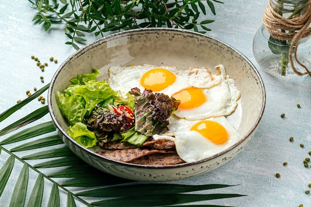 Gourmet fried eggs with roast beef and salad