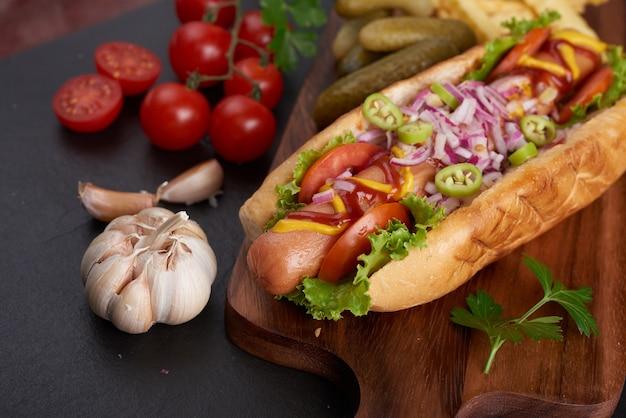 Гурман приготовил хот-дог из говядины с гарнирами и чипсами. вкусные и простые хот-доги с горчицей, перцем, луком и начос. хот-доги полностью загружены разными начинками на доске для весла.
