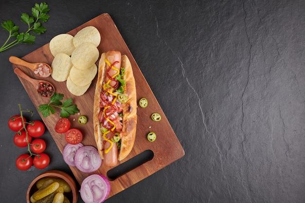 Hot dog di manzo alla griglia gourmet con lati e patatine. deliziosi e semplici hot dog con senape, pepe, cipolla e nachos. hot dog completamente caricati con condimenti assortiti su una tavola da paddle.