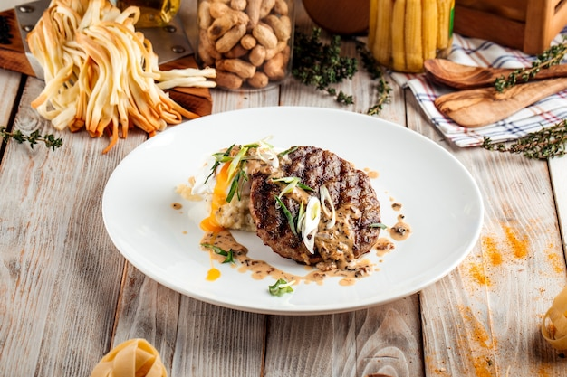 Изысканная котлета на гриле с грибным соусом на деревянном столе