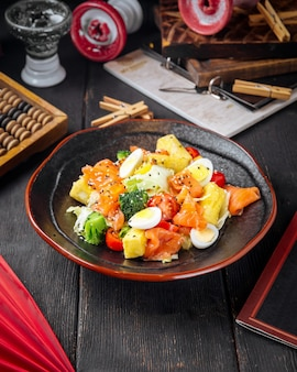 暗い木製のテーブルに卵と野菜のグルメ健康料理サーモン