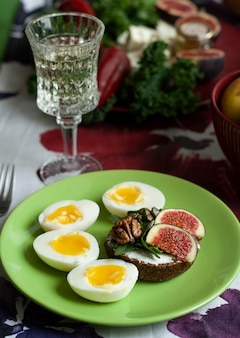 A gourmet lunch: a rye bread sandwich, cheese bites, sliced figs and boiled eggs.
