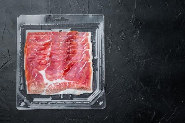 Gourmet, manually sliced jamon set, on black table, flat lay