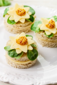 Gourmet mini sandwiches of bread with cheese, herbs and sweet mustard