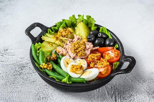 鍋に野菜、卵、マグロ、アンチョビを入れたグルメニコイズサラダ。白色の背景。上面図。