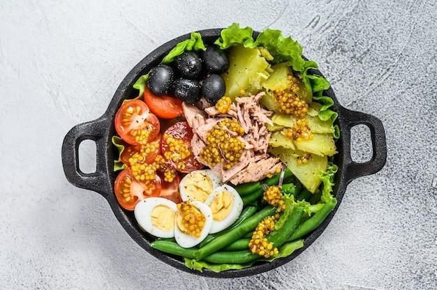 鍋に野菜、卵、マグロ、アンチョビを添えたグルメニコイズサラダ