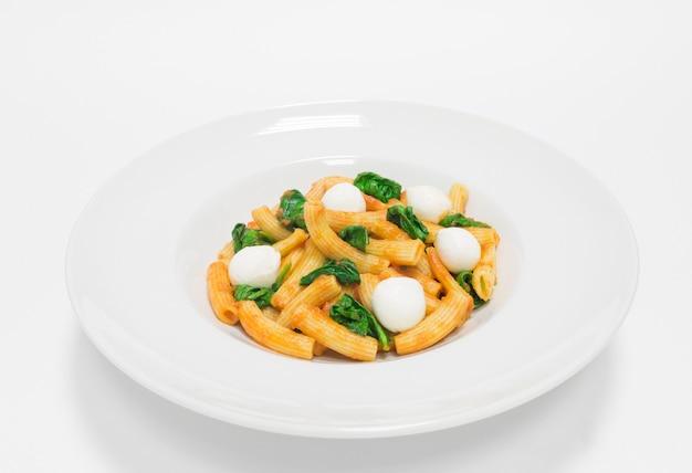 바질과 모짜렐라 볼을 곁들인 고급 파스타. 평면도. 흰색 배경. 건강한 먹는 개념. 혼합 매체