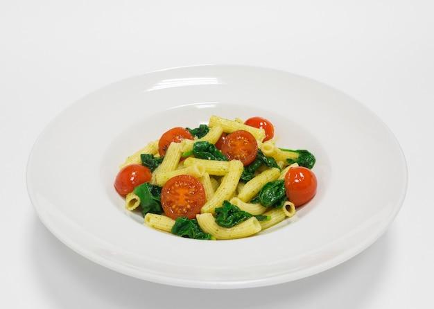 체리 토마토, 바질, 페스토를 곁들인 미식가 파스타. 평면도. 흰색 배경. 건강한 먹는 개념. 혼합 매체
