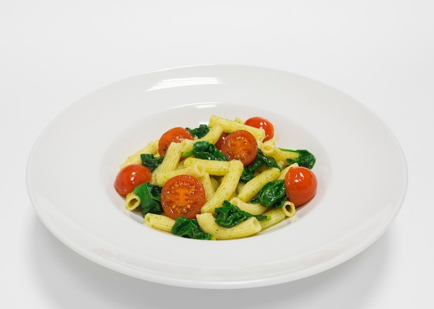 Gourmet pasta with cherry tomatoes, basil and pesto. top view. white background. healthy eating concept. mixed media