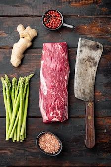 오래 된 어두운 나무 테이블에 오래 된 정육점 칼로 원시 신선한 대리석 쇠고기 등심 세트의 미식가 부분,