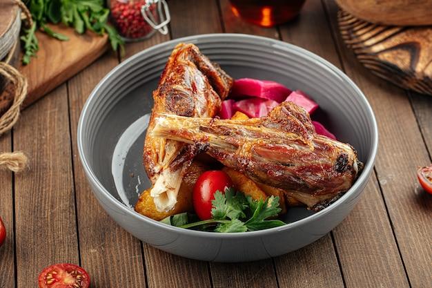 Гурман приготовил блюдо из бараньих ножек с овощами на деревянном фоне