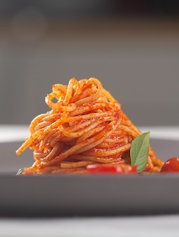 Gourmet restaurant dish pasta in tomato sauce with cherry tomatoes and basil