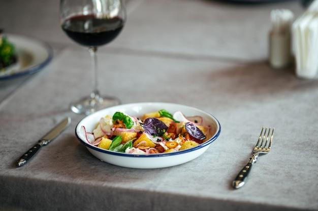 Изысканный салат с крекерами и овощами на сервированном столе с бокалом красного вина