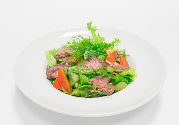 로스트 비프, 절인 오이, 겨자를 곁들인 고메 샐러드. 평면도. 흰색 배경. 건강한 먹는 개념. 혼합 매체