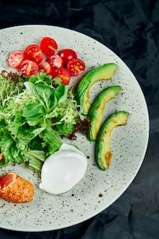 Салат для гурманов с жареным лососем, сливочным соусом, авокадо, шпинатом, листьями салата, моцареллой и помидорами черри на черном. вкусный салат из морепродуктов. закрыть