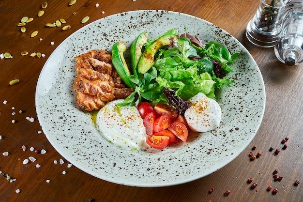 Изысканный салат с жареным лососем, сливочным соусом, авокадо, шпинатом, салатом, моцареллой и помидорами черри на деревянном столе. вкусный салат из морепродуктов. закрыть