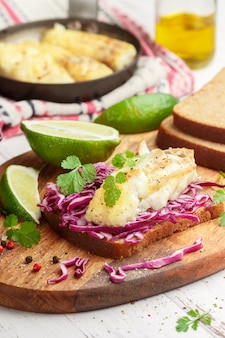 Gourmet sandwich of rye bread, fried or baked white fish (cod, pollock, nototenia, hake, perch) and red cabbage salad