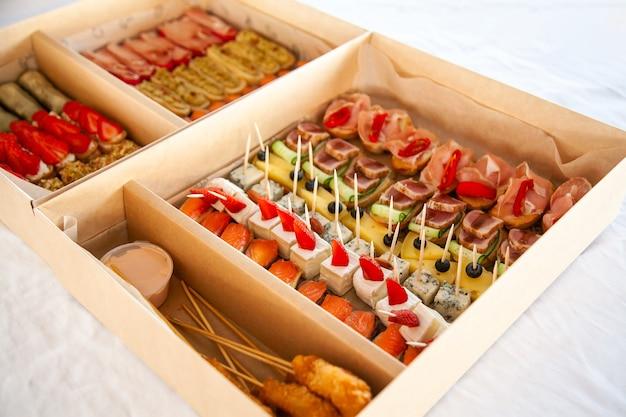 Изысканные закуски в картонной коробке для фуршета для вечеринки.