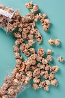 Изысканный сладкий попкорн в пластиковой чашке. карамельный аромат. вид сверху