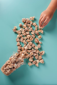 Изысканный сладкий попкорн в пластиковой чашке. карамельный аромат. с детской рукой, ловящей попкорн. вид сверху