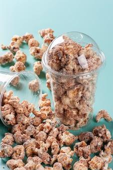 Изысканный сладкий попкорн в пластиковой чашке. карамельный аромат.