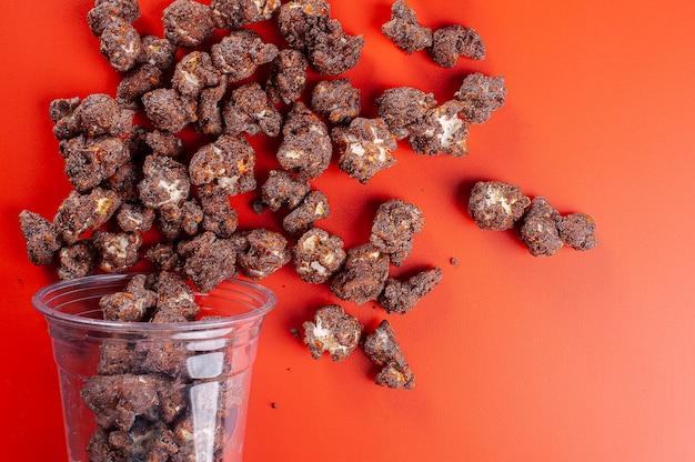 Изысканный сладкий попкорн в пластиковой чашке. шоколадный аромат. вид сверху